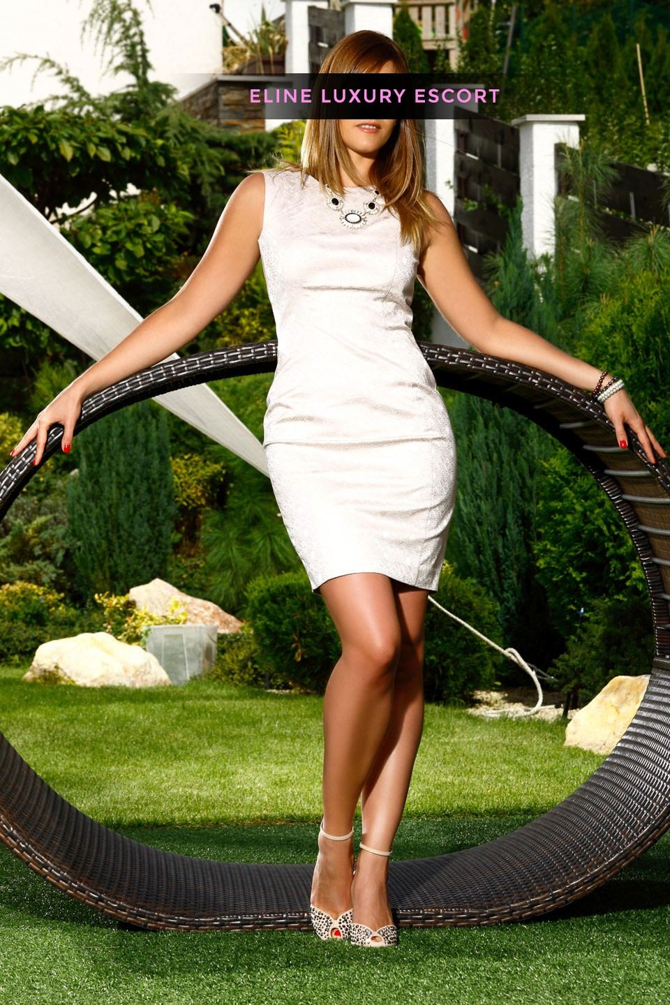 In garden with white dress and white heels